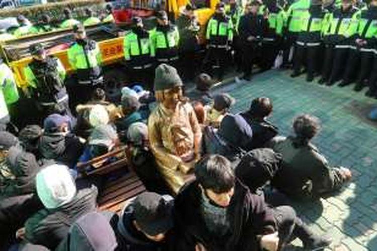 Foto ini diambil pada 28 Desember 2016. Tampak para aktivis, dalam pengawalan ketat polisi, duduk mengeliling patung simbol budak seks yang dipasang di depan kantor Konsulat Jenderal Jepang di Busan, kota pelabuhan di Korea Selatan (Korsel).