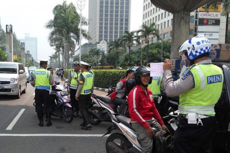 Jajaran aparat kepolisian dari Direktorat Lalu Lintas Polda Metro Jaya menggelar Operasi Patuh Jaya 2016 di Jalan Asia Afrika, Senayan, Jakarta pada Jumat (20/5/2016).