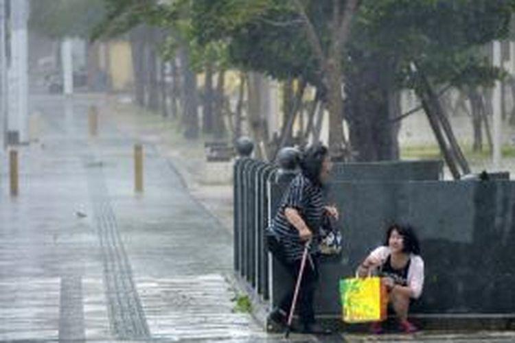 Dua perempuan warga kota Naha, Okinawa, Jepang berlindung dari terjangan badai Neoguri yang menghantam pulau berpenduduk 1,2 juta jiwa itu.