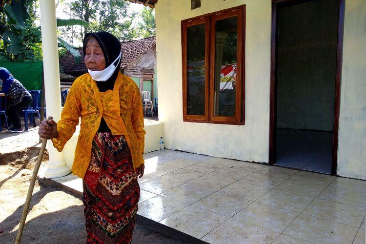 Tukinem berdiri di depan rumahnya di Desa Boro, Kecamatan Selorejo, Kabupaten Blitar yang telah selesai direnovasi oleh Polres Blitar, Jumat (2/7/2021)