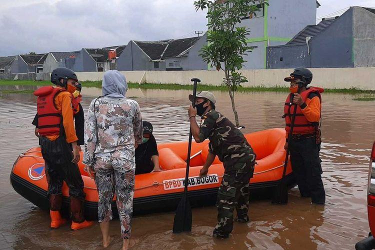 Sejumlah petugas BPBD Kabupaten Bogor sedang mengevakuasi warga yang terdampak banjir di Kabupaten Bogor, Jawa Barat, Jumat (19/2/2021).