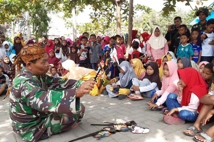 Serma Paijan Babinsa Kalikondang, Kabupaten Demak , Jateng,  memperlihatkan kemampuannya mendalang di depan anak - anak, di sela - sela kegiatan TMMD, Jumat (19/7/2019) siang.