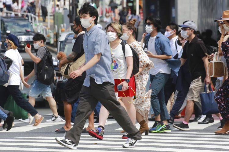 Orang-orang yang memakai masker untuk membantu melindungi diri dari penyebaran virus corona berjalan melintasi persimpangan di Tokyo, Senin, 30 Agustus 2021.