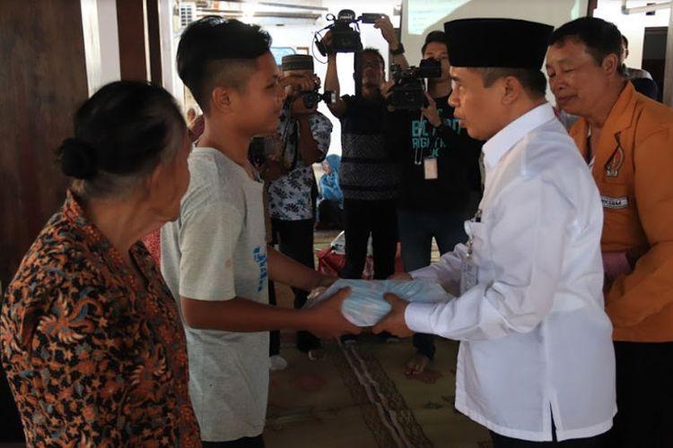 Wakil Bupati Gunungkidul, Immawan Wahyudi Menyerahkan Bantuan WKSBM kepada anak sekolah kurang mampu di Balai Desa Baleharjo.
