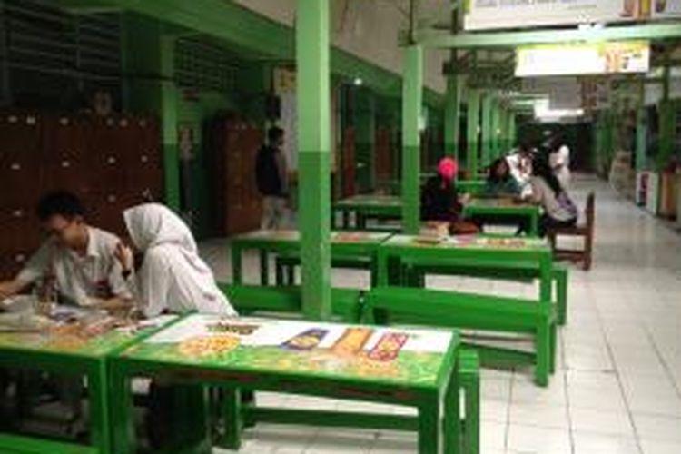 Beberapa murid kelas 12 SMA Negeri 78, Jakarta Barat, berkumpul di kantin sembari menunggu Ujian Nasional (UN) berbasis komputer, Senin (13/4/2015) pagi. Berbeda dengan pelaksanaan UN pada umumnya, kali ini para murid terlihat senang dan tidak banyak yang membawa buku untuk belajar lagi. Kebanyakan mereka hanya bercanda dan mengobrol satu sama lain.