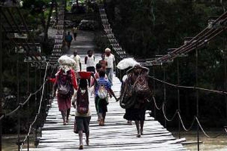 Warga menyeberangi jembatan gantung di Distrik Bolakme, Jayawijaya, Papua, Jumat (6/12/2013).