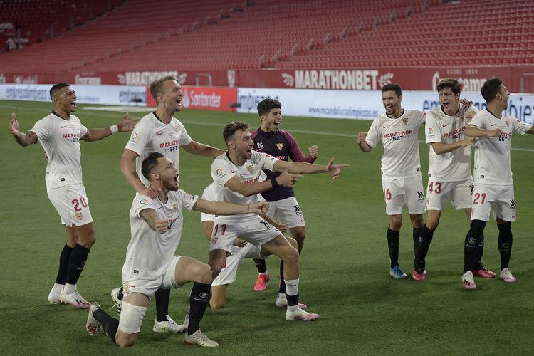 Para pemain Sevilla merayakan pada akhir pertandingan sepak bola Liga Spanyol antara Sevilla FC dan Real Betis di stadion Ramon Sanchez Pizjuan di Seville pada 11 Juni 2020.