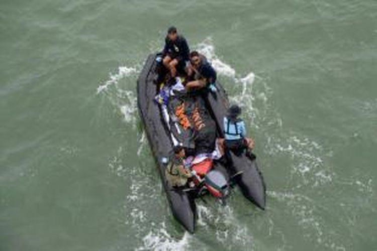 Anggota Pasukan Katak dan penyelam dari TNI AL menangani jenazah korban jatuhnya pesawat AirAsia QZ8501 dari perahu menuju KRI Banda Aceh dalam operasi pencarian di Laut Jawa, dekat perairan Pangkalan Bun, Kalimantan Tengah, Sabtu (3/1/2015).