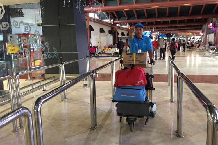 Petugas airport helper sedang membawa barang penumpang dengan troli di Terminal 2 Bandara Soekarno-Hatta, Tangerang, Selasa (10/10/2017). Jasa airport helper diberikan bagi penumpang secara cuma-cuma dan petugas dilarang menerima uang tip dari penumpang.