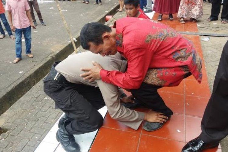 Bripda Asrul (20) langsung mencium kedua kaki ayahnya, Syamsuar (45) usai resmi jadi polisi, Selasa (6/2/2018). Anak dari pekerja pemecah batu itu tersungkur di depan ayahnya setelah mengikuti pelantikan Brigadir muda di SPN Batua, Makassar.
