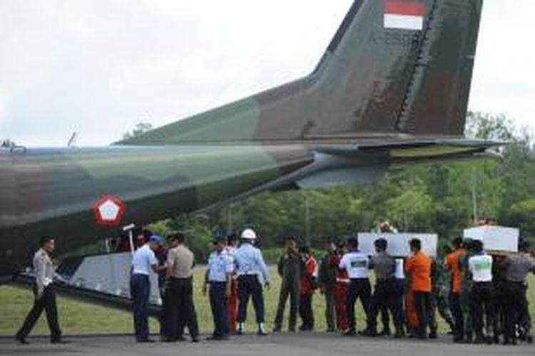Petugas membawa peti jenazah korban AirAsia QZ 8501 menuju pesawat di Lapangan Udara Iskandar, Pangkalan Bun, Kalimantan Tengah, Rabu (7/1/2015). Sebanyak dua jenazah tersebut akan dibawa ke Surabaya untuk diidentifikasi.