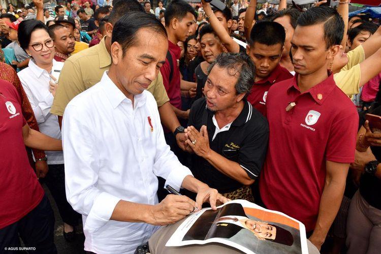 Presiden Joko Widodo membubuhkan tanda tangan di atas selembar foto yang diberikan warga Bali, Jumat (14/6/2019). Uniknya, alas foto itu adalah punggung asisten ajudan AKP Syarif Muhanmad Fitriansyah.