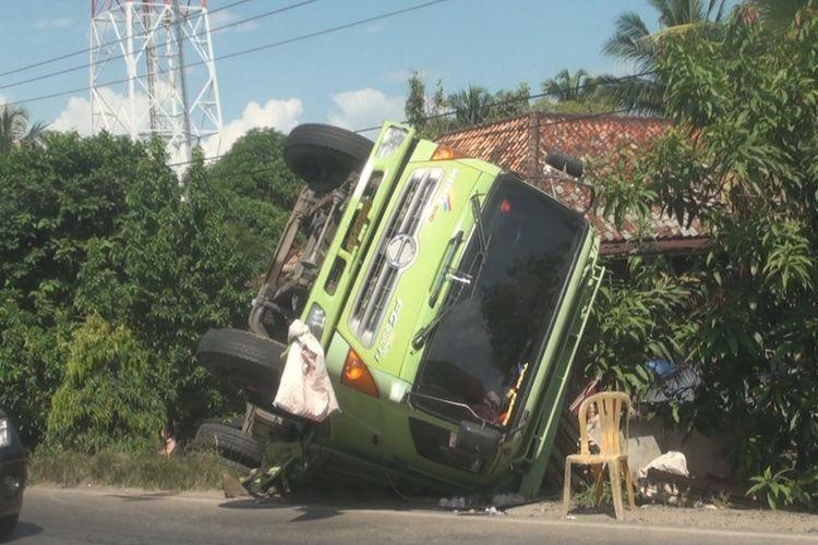 Truk fuso penuh muatan kaca yang terjungkal di sisi jalan lintas timur  Palembang-Ogan Ilir akibat menghindari tabrakan. Ratusan keping kaca pecah akibat kejadian itu