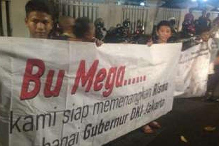 Pendukung Tri Rismaharini yang tergabung dalam Gerak Indonesia membentangkan spanduk dikungan agar Wali Kota Surabaya tersebut maju ke Pilgub Jakarta tahun depan, Kamis (21/7/2016) malam.