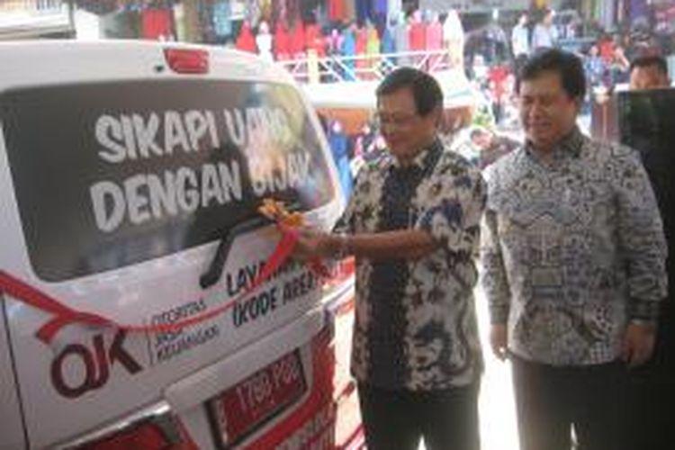 Otoritas Jasa Keuangan (OJK) menghelat kampanye program literasi atau pemahaman keuangan untuk masyarakat bersama Bank Danamon di Pasar Baru Kota Bekasi di Jalan Juanda pada Senin (5/5/2014). Direktur Utama Bank Danamon Henry Ho (kiri) dan Direktur Literasi dan Edukasi OJK Agus Sugiarto (kanan) saat meresmikan Si Molek (Mobil Literasi Keuangan). Untuk tahap awal, tersedia 20 unit mobil yang menjadi sarana kampanye pada 14 kota di seluruh Indonesia. Kampanye berlangsung sejak Senin ini sampai dengan Minggu (11/5/2014).
