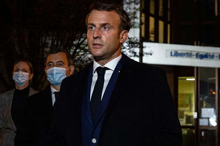 French President Emmanuel Macron (right) talks to the press in front of the high school in Paris Conflans Saint-Honorine where teacher Samuel Paty taught. A Muslim extremist beheaded Paty for showing his students cartoons from Charlie Hebdo mocking the Prophet Muhammad