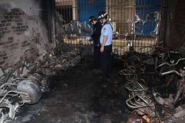 Petugas pemadam kebakaran dan polisi memeriksa sisa-sisa skuter yang hangus dalam insiden kebakaran di gedung asrama mahasiswa di Guangxi, China, Minggu (5/5/2019).