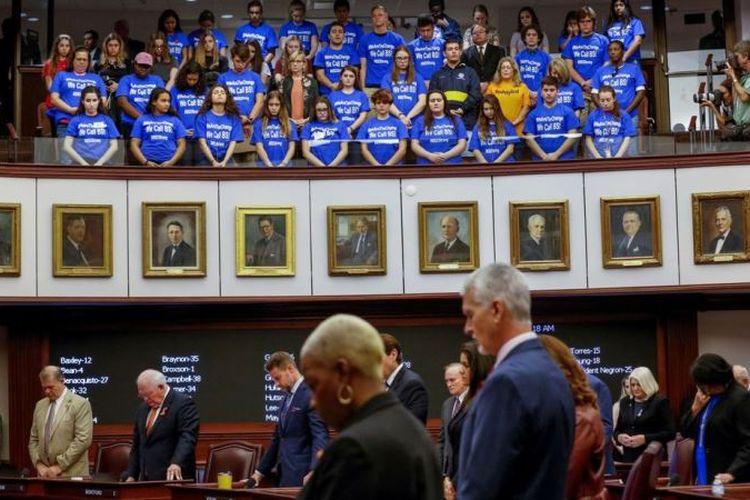 Anggota Senat Florida, dan beberapa siswa korban penembakan SMA Marjory Stoneman Douglas mengheningkan cipta sebelum sidang Senin (5/3/2018). Senat mengesahkan undang-undang yang menaikkan batas usia calon pembeli senjata, dan mengizinkan sebagian guru membawa senjata ke sekolah (Sky News).