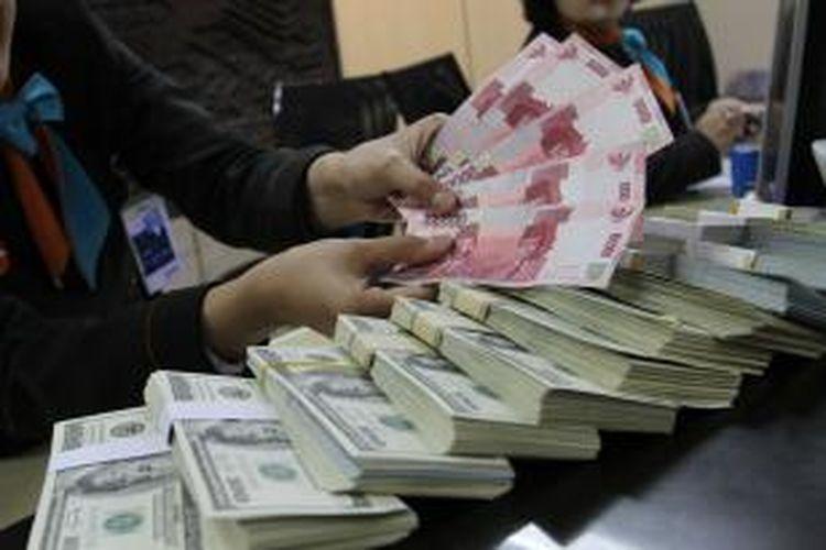 Teller sebuah bank di Jakarta Selatan menghitung uang rupiah di atas dolar Amerika Serikat, Jumat (24/1/2014).