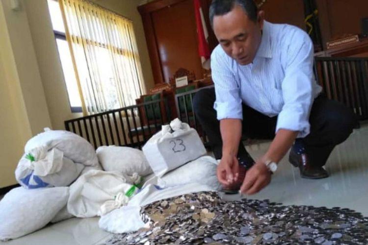 Kuasa hukum Dwi Susilarto, Sutarto, menunjukkan uang mutah dan nafkah yang dibayarkan kliennya setelah gugatan cerainya dikabulkan di Pengadilan Agama Karanganyar, Kamis (23/8/2018).