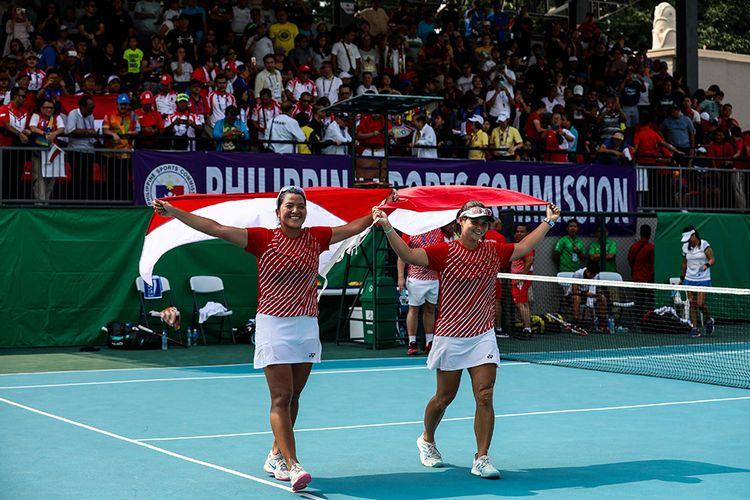 Pasangan ganda putri timnas tenis Indonesia, Beatrice Gumulya (kanan) dan Jessy Rompies mengekspresikan kemenangan dengan mengangkat bendera Merah Putih usai memenangkan babak Final ganda putri saat melawan pasangan dari Thailand, Peangtarn Plipuech/Tamarine Tanasugarn di Rizal Memorial Tennis Centre, Manila, Filipina, Sabtu (7/12/2019). Beatrice/Jessy meraih medali emas ganda putri pada SEA Games 2019, dengan mengalahkan unggulan kedua dari Thailand, Peangtarn Plipuech/Tamarine Tanasugarn, 6-3, 6-3.