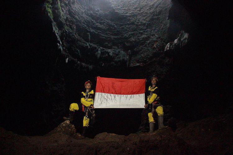 Penelusur goa Mapala UI mengibarkan bendera Merah Putih di dasar Goa Grubug, Gunungkidul, Yogyakarta.