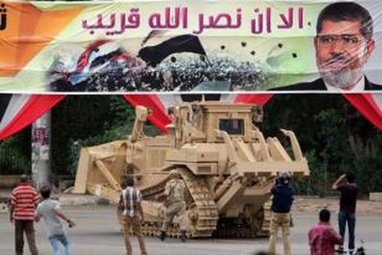 Buldoser militer Mesir membongkar kamp pengunjuk rasa di Alun-alun Al-Nahda Kairo, setelah pasukan keamanan Mesir membubarkan pendukung Presiden Mesir terguling Muhamamd Mursi, 14 Agustus 2013.