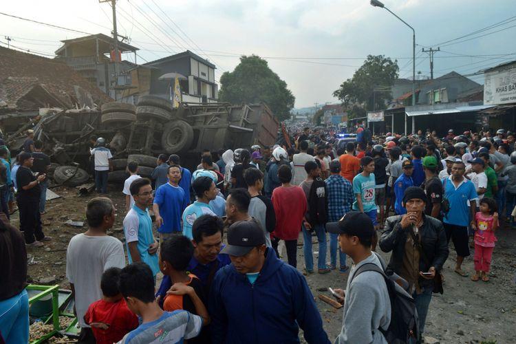 Sejumlah warga melihat truk yang mengalami kecelakaan di jalur tengah Tegal-Purwokerto, Desa Jatisawit, Bumiayu, Brebes, Jawa Tengah, Minggu (20/5/2018). Truk pengangkut gula yang diduga mengalami rem blong tersebut menabrak enam rumah, satu kios buah, 19 sepeda motor, dua mobil sehingga mengakibatkan 11 orang meninggal dan sejumlah warga luka-luka. ANTARA FOTO/Zaenal/ol/kye/18