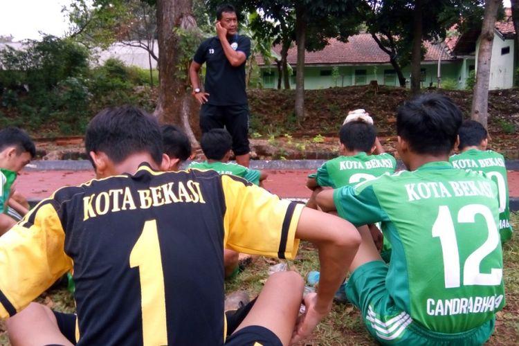 Kiper SSB Candrabhaga Sendy Permana (nomor punggung 1) dan penyerang Gregorio Veda Ezra (nomor punggung 12) mendengarkan arahan pelatih Tias Tono Taufik pada turnamen U15 Jakarta Timur pada Sabtu (27/10/2018) di Lapangan Brigif 1. Pembinaan usia muda adalah hal penting untuk kemajuan persepakbolaan di Indonesia.