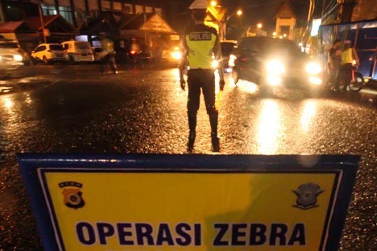 Polisi lalu-lintas menghentikan pengendara sepeda motor saat Operasi Zebra Rencong 2019 di lintas Nasional Medan-Banda Aceh, Lhokseumawe, Aceh, Sabtu 26/10/2019).  Selain sasaran tujuh poin utama tilang pelangaran lalu lintas, Operasi Zebra menjelang tengah malam itu juga menyasar senjata api, senjata tajam, bahan peledak, identitas diri (DPO Polisi) dan peredaran narkotika.