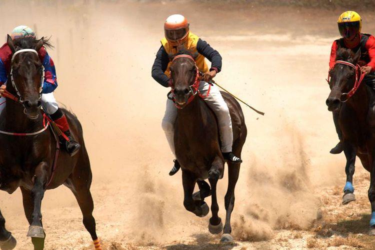 Joki beradu kecepatan saat mengikuti lomba pacuan kuda tradisional di Desa Kalimporo, Jeneponto, Sulawesi Selatan, Sabtu (27/10/2018). Pacuan kuda tradisional ini terbilang unik karena jokinya bukan hanya orang dewasa tapi juga diikuti joki anak-anak yang hanya menggunakan peralatan seadanya bahkan tidak sedikit hanya menggunakan sandal.