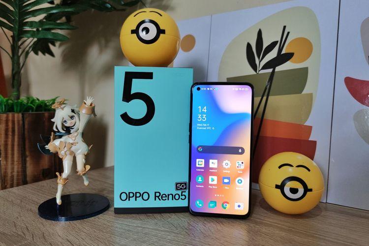 Oppo Reno5 5G bersama kotak penjualannya. Sekilas, desain kotak kemasan ponsel ini memang berbeda dengan pendahulunya, Reno4. Namun, tampilannya masih seirama dengan Reno5. Alih-alih hijau pinus pekat, kotak penjualan Reno5 5G kini dilapisi dengan warna hijau toska yang adem di mata. Ponsel ini juga terasa ringan dan nyaman digenggam dan memiliki layar yang cukup lega.