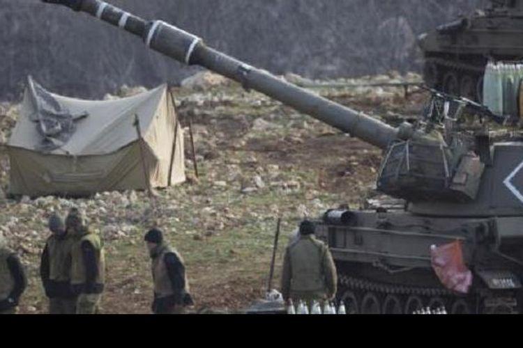 Tentara Israel berdiri dekat unit artileri bergerak di Dataran Tinggi Golan dekat perbatasan dengan Suriah (28/1).