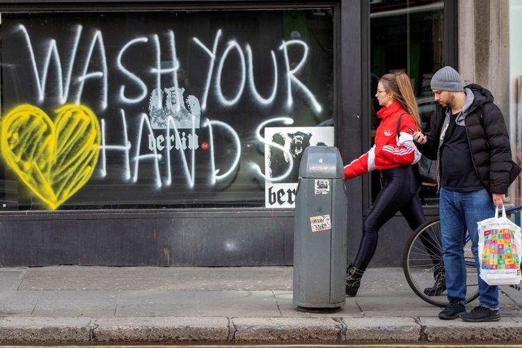 Pejalan kaki melintas di depan grafiti yang berisikan pesan untuk mencuci tangan di Dublin, Irlandia, 13 Maret 2020. Pandemi Covid-19 yang disebabkan oleh virus corona menjadi insipirasi seniman grafiti untuk memberikan peringatan dan motivasi bagi warga dalam menghadapi virus tersebut.