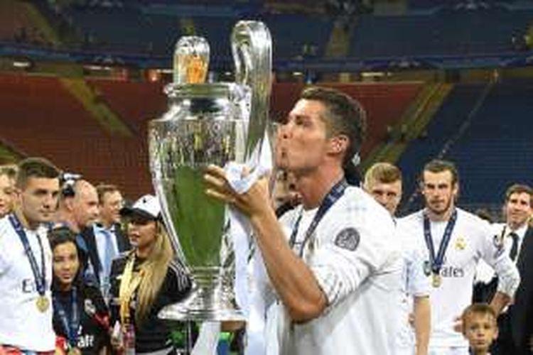 Cristiano Ronaldo mencium trofi Liga Champions seusai mengantarkan Real Madrid menang adu penalti atas Atletico di San Siro, Sabtu (28/5/2016).