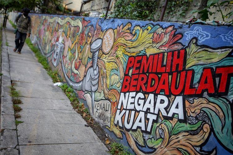 Warga melintas di depan mural bertema pemilihan umum di kawasan Pasar Anyar, Kota Tangerang, Banten, Kamis (7/5/2020). Presiden Joko Widodo menunda pemungutan suara Pemilihan Kepala Daerah (Pilkada) 2020 hingga Desember 2020 akibat wabah COVID-19. ANTARA FOTO/Fauzan/aww.