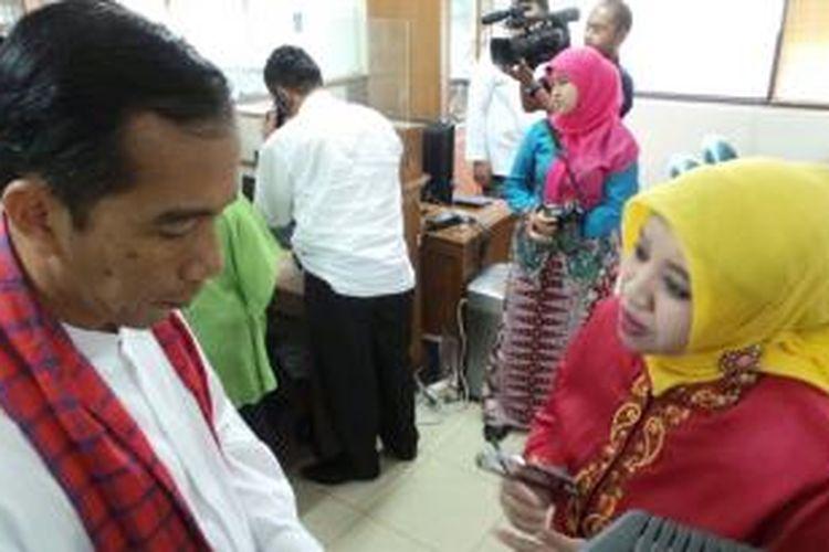 Gubernur DKI Jakarta Joko Widodo (kiri) berbincang dengan Kepala Pelayanan Terpadu Satu Pintu Jakarta Timur Husnul Khotimah, Jumat (18/10/2013).