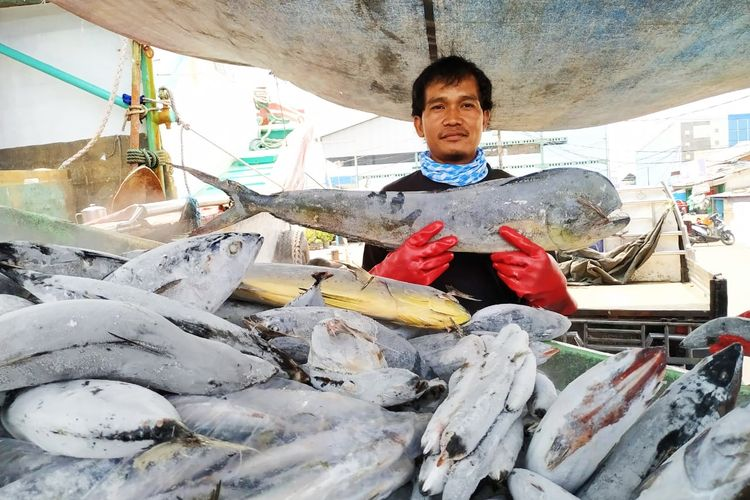 Nelayan membawa hasil perikanan