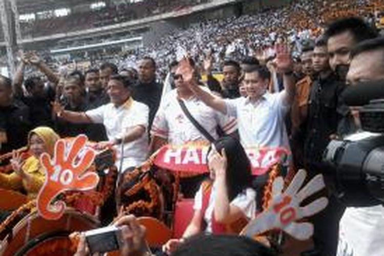 Pasangan bakal calon presiden dan wakil presiden Partai Hanura, Wiranto (kiri) dan Hary Tanoesoedibjo (kanan), naik becak bersama istri masing-masing saat memasuki arena kampanye di Gelora Bung Karno, Jakarta, Sabtu (5/4/2014). Wiranto dan Harry menggowes becak di belakang, sementara sang istri duduk di kursi depan.