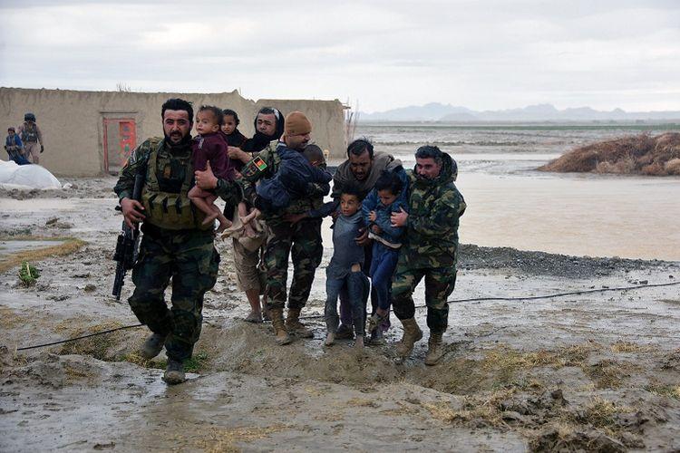 Anggota pasukan keamanan Afghanistan membawa anak-anak korban banjir yang menerjang di Distrik Arghandab, Provinsi Kandahar, pada Sabtu (2/3/2019). Setidaknya 20 orang tewas menurut data PBB.