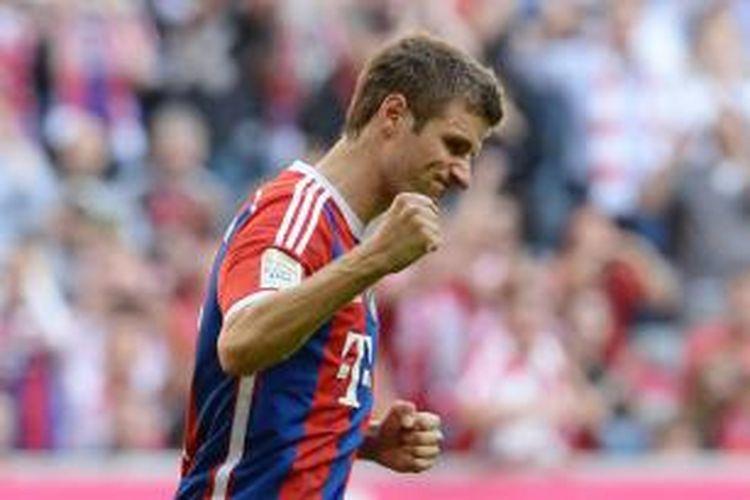 Penyerang Bayern Muenchen, Thomas Mueller, merayakan keberhasilan mencetak gol ke gawang Werder Bremen, pada pertandingan Bundesliga, di Allianz Arena, Sabtu (18/10/2014).