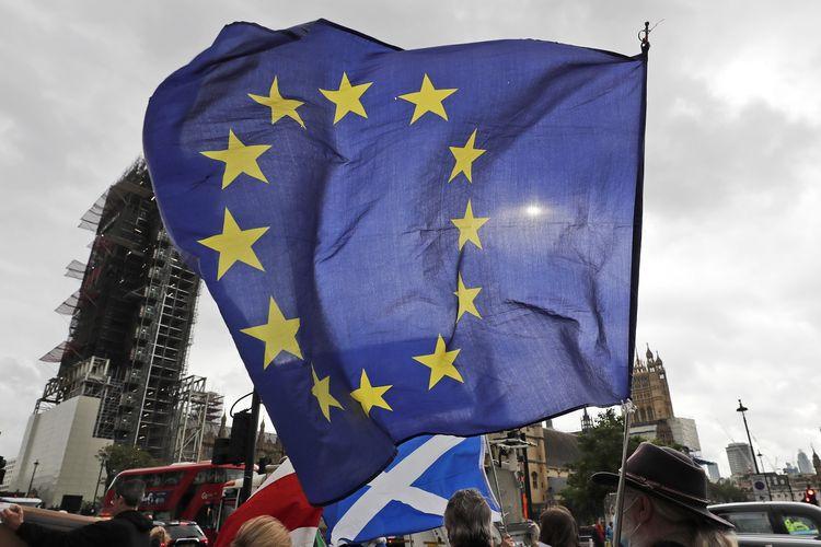 Seorang pendukung Uni Eropa mengibarkan bendera di depan kantor parlemen London, Inggris, Rabu (30/9/2020), saat berlangsungnya putaran ke-9 pembicaraan dagang antara Uni Eropa dengan Inggris di Brussels, Belgia, tentang RUU Pasar Internal Inggris yang kontroversial.