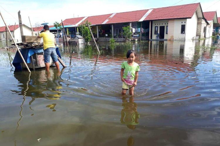 Aulia, salah satu anak di Desa Buhu Kabupaten Gorontalo harus melintasi genangan air di sekitar rumahnya untuk bisa bermain di rumah tetangganya. luapan air Danau Limboto telah menggenangi permukiman warga sejak 2 bulan lalu.