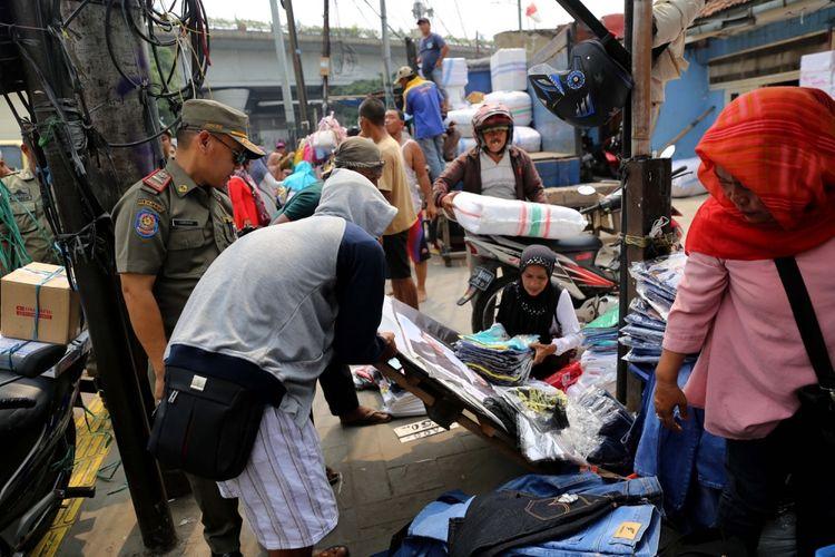 Petugas Satpol PP melakukan penertiban pedagang kaki lima (PKL) yang berjualan di Kawasan Pasar Tanah Abang, Jakarta, Rabu (17/5/2017). Penertiban dilakukan setiap hari menyusul mulai banyaknya PKL yang berjualan di trotoar dan jalan kawasan Pasar Tanah Abang.