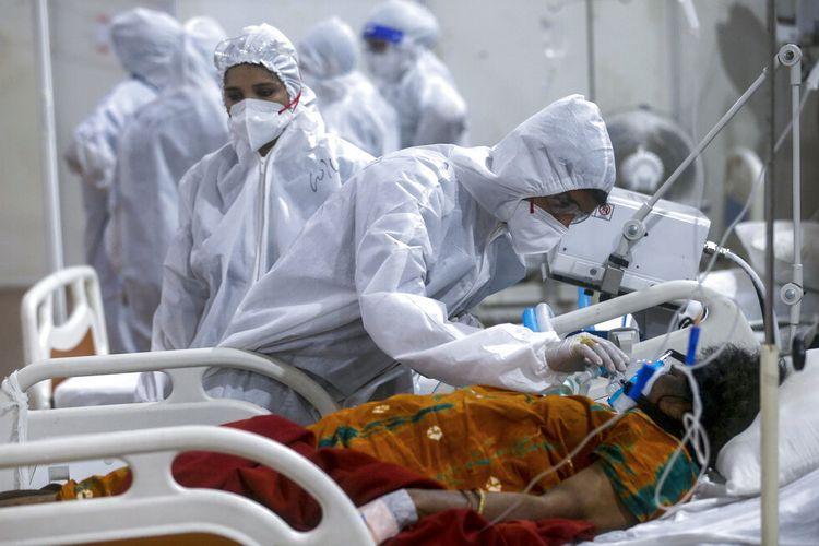 Pada file foto 6 Mei 2021 ini, petugas kesehatan mencoba menyesuaikan masker oksigen seorang pasien di rumah sakit lapangan jumbo BKC, salah satu fasilitas COVID-19 terbesar di Mumbai, India.
