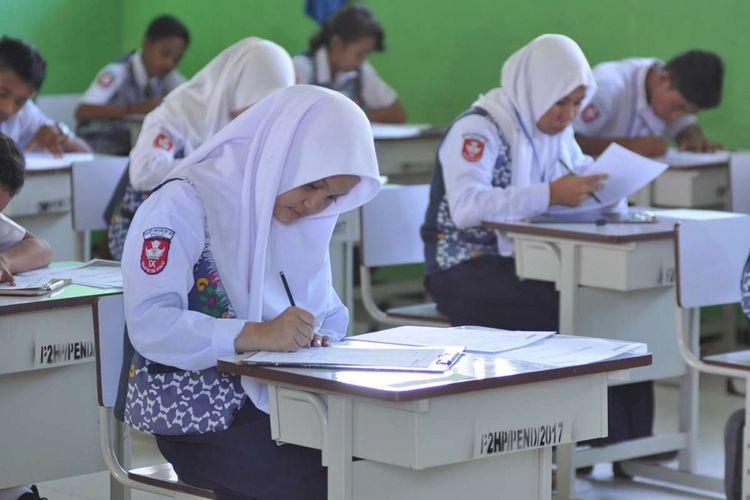 Sejumlah pelajar SMP Negeri 18 Palu mengerjakan soal ujian nasional dengan skema ujian nasional berbasis kertas dan pensil (UNKP) di SMP Negeri 18 Palu, Kelurahan Mamboro, Palu Utara, Sulawesi Tengah, Senin (23/4/2018). Sebagian sekolah SMP di Kota Palu belum dapat melaksanakan ujian nasional berbasis komputer (UNBK) karena keterbatasan fasilitas terutama komputer.