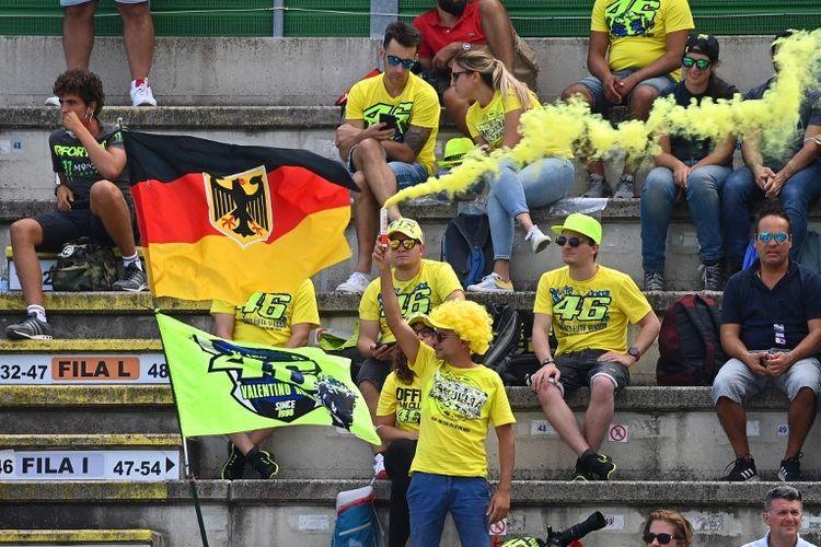 Suporter Valentino Rossi menyalakan cerawat pada sesi kualifikasi MotoGP San Marino 2021, Sabtu (18/9/2021).