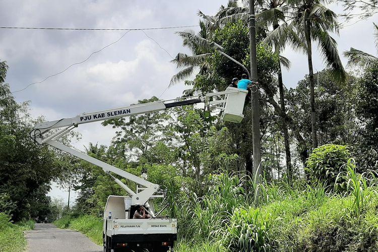 Petugas Penerangan Jalan Umum (PJU) Dinas Perhubungan Kabupaten Sleman saat memasang lampu di jalur evakuasi Dusun Singlar.
