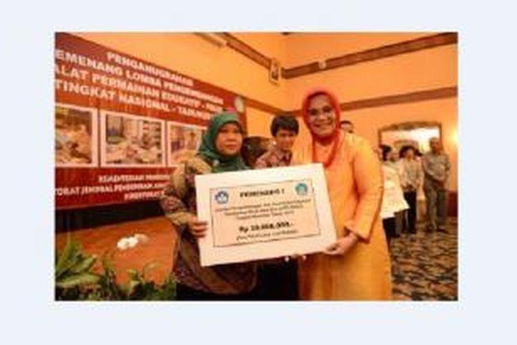 Puji Riswati (kiri) bersama Direktur Jenderal Pendidikan Anak Usia Dini, Nonformal, dan Informal Kemdikbud Lydia Freyani Hawadi saat menerima hadiah RP 25 juta di Gedung Kementerian Pendidikan dan Kebudayaan, Jakarta, Kamis (24/10/2013).