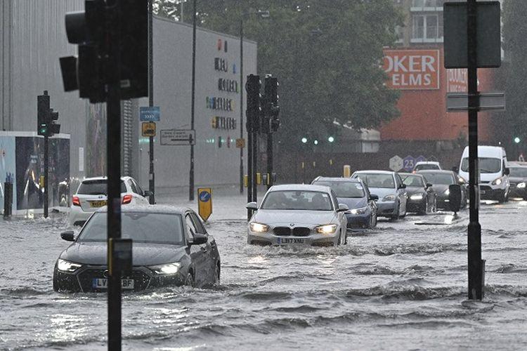 Bus dan mobil yang terendam banjir di jalan-jalan di London pada Minggu (25/7/2021), ketika badai petir berulang kali melanda ibu kota Inggris. [JUSTIN TALLIS/AFP]